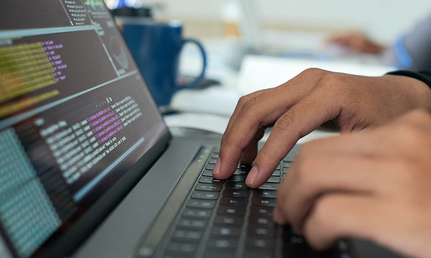 Person typing coding on their laptop