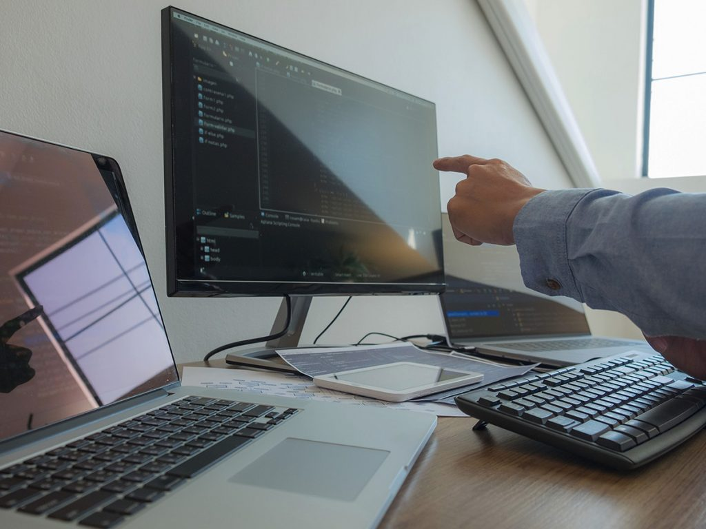 An employee pointing at one of two work screens.